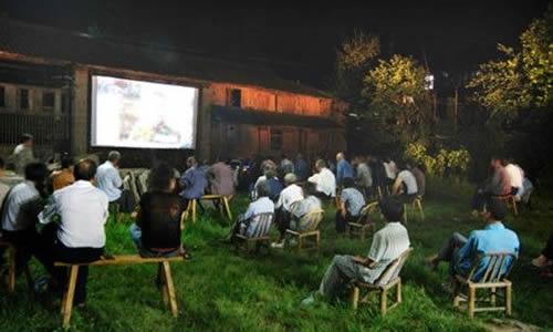 到了三安园,我看到两根电线杆中间挂着一块很大的布,正在放电影,荧幕